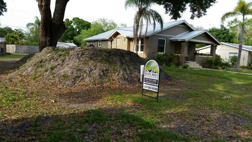 Dirt mound and Sun Bay Builders sign